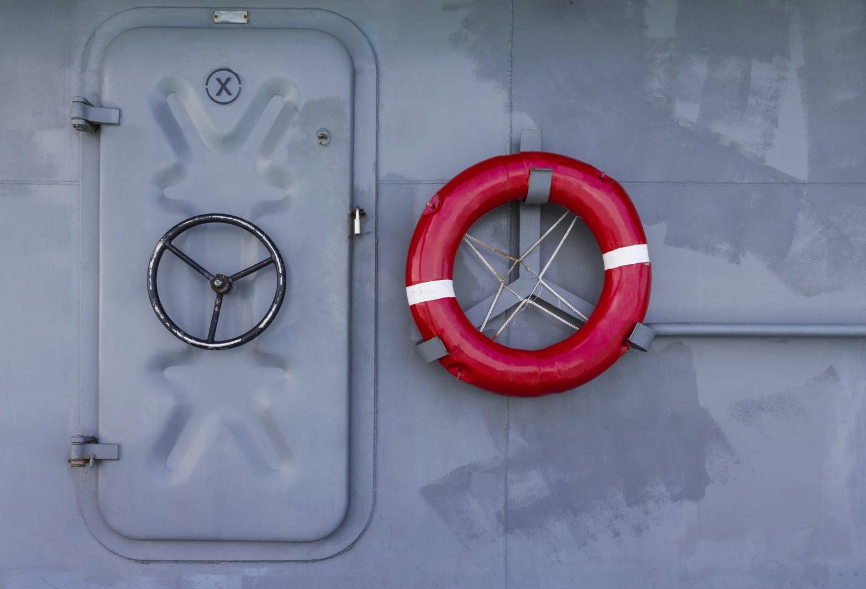 Stählerne Tür auf Boot mit Rettungsring