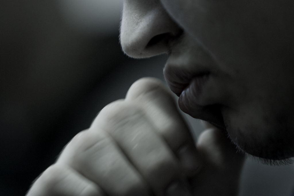Jugendlicher führt Faust zum Mund