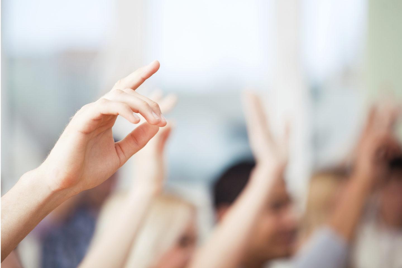 Hände melden sich im Unterricht