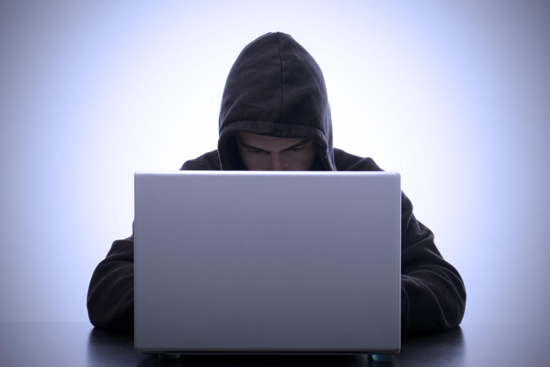 Jugendlicher mit Kapuze sitzt vor einem Laptop