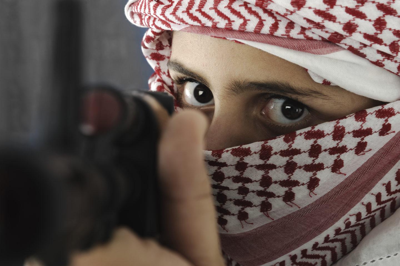 Vermummter Mann zielt mit Gewehr, von vorn fotografiert
