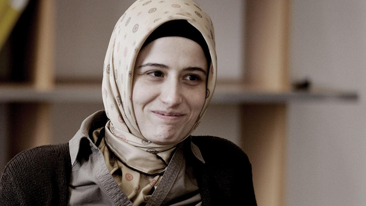 Junge Frau mit Kopftuch lächelt