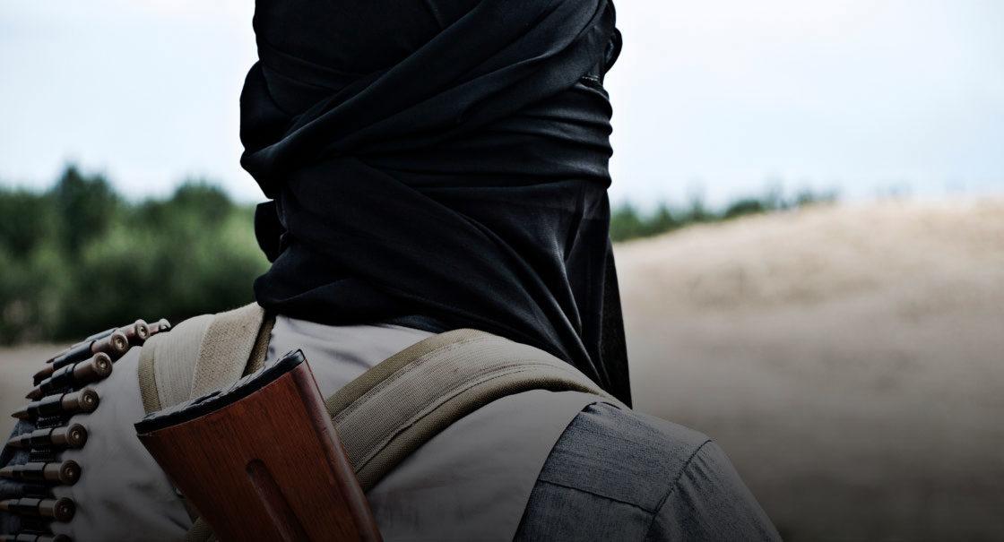 Vermummter Mann mit Waffe von hinten