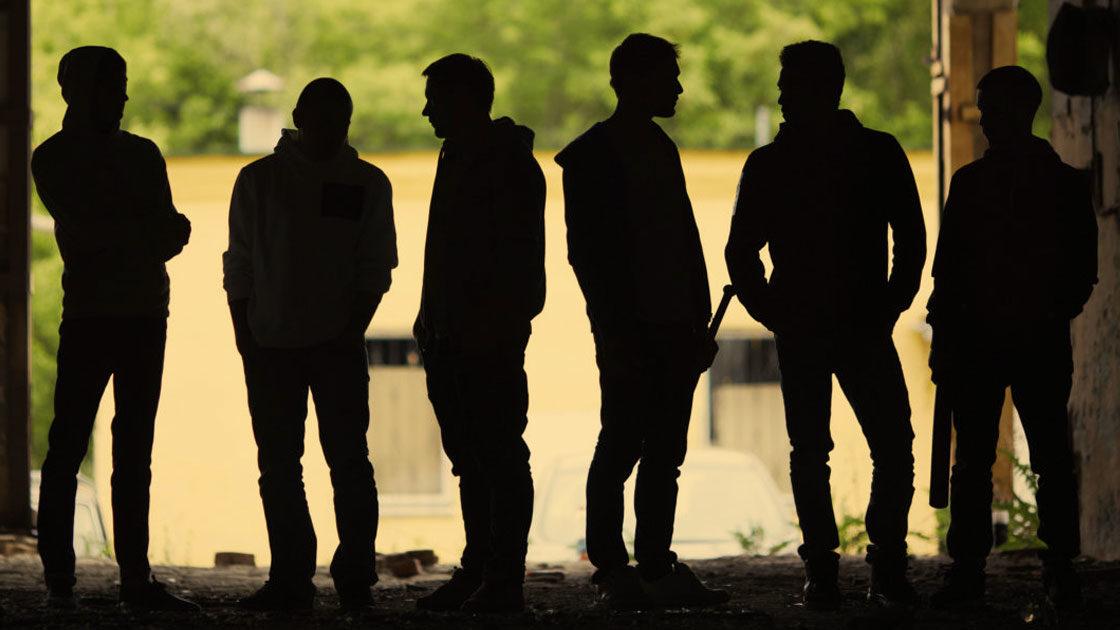 Sechs junge Männer stehen bedrohlich mit Baseballschläger zusammen