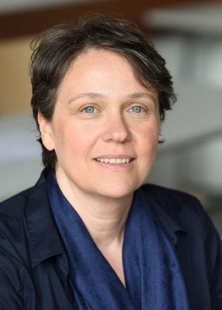 Portrait von Judy Korn - sie sitzt und lächelt, von vorn fotografiert