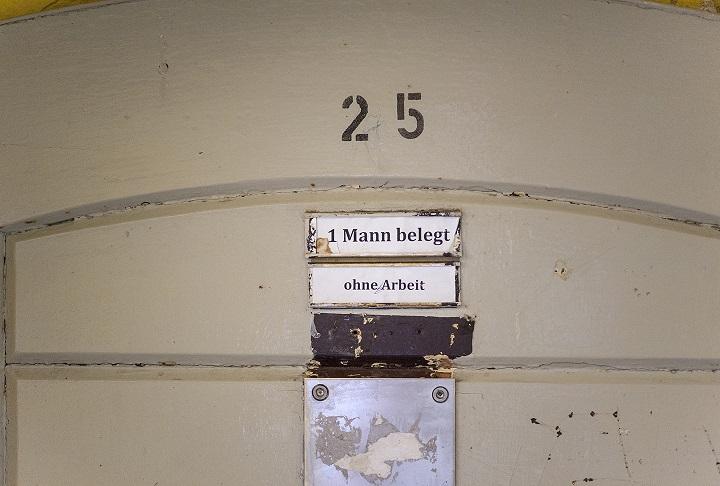 Schild mit Aufschrift 1 Mann belegt in Haftanstalt