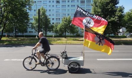 Mann fährt Fahrrad mit zwei Deutschlandfahnen