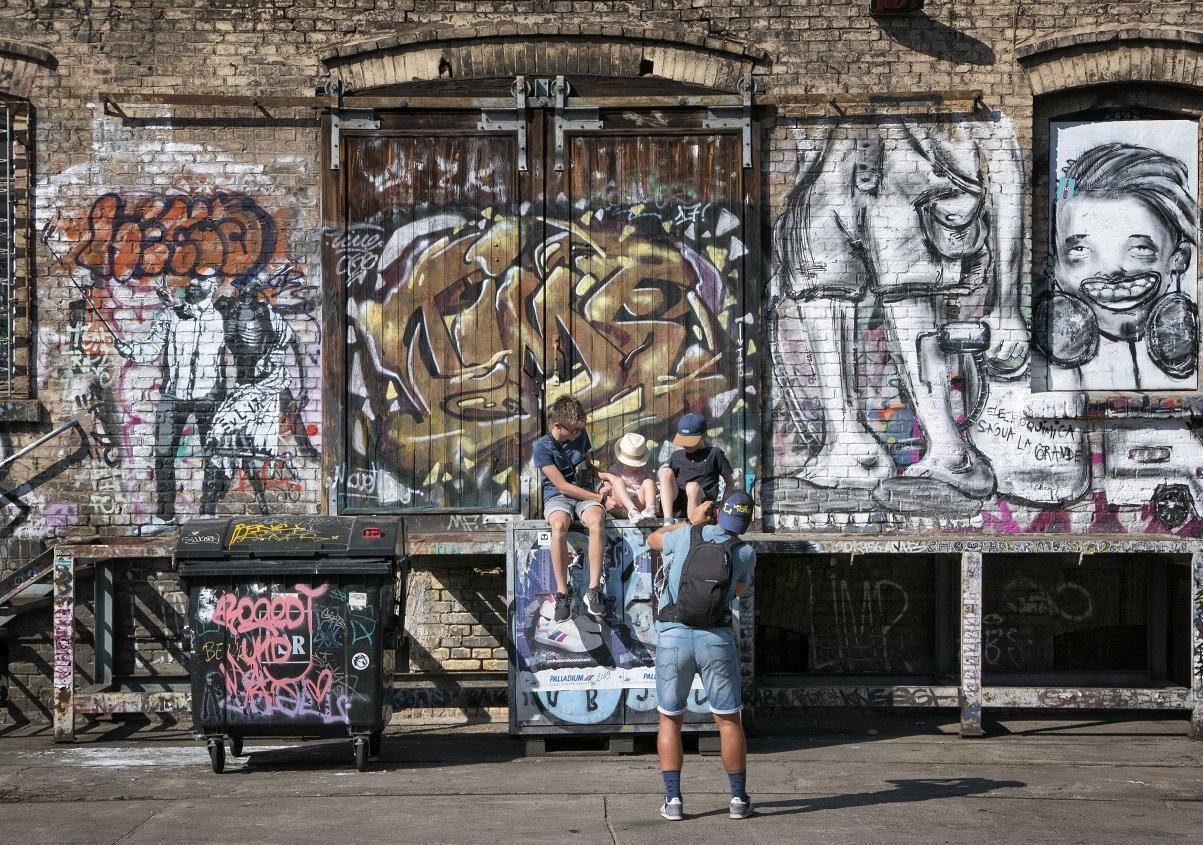 Drei junge Menschen sitzen vor einer bunte Wand, ein Mann fotografiert sie