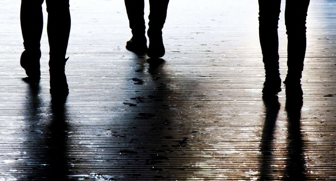 Drei Paar Beine laufen in dunkler Straße