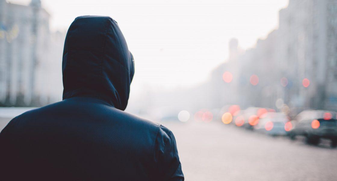 Mensch mit Kapuze von hinten blickt auf Straße